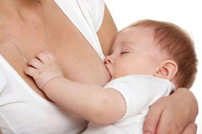 маленький ребенок на руках у мамы сосет грудь