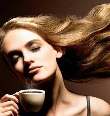красивая девушка с длинными развивающимися волосами наслаждается ароматом кофе