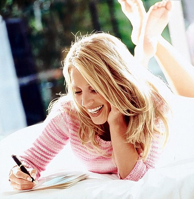 женщина, лежа на животе, пишет ручкой на тетради