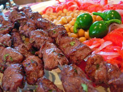 шашлык с зеленью, помидорами, луком и кукурузой на тарелке