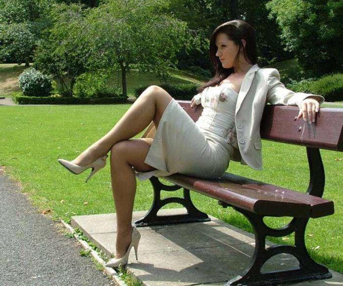 красивая девушка сидит на лавочке нога на ногу