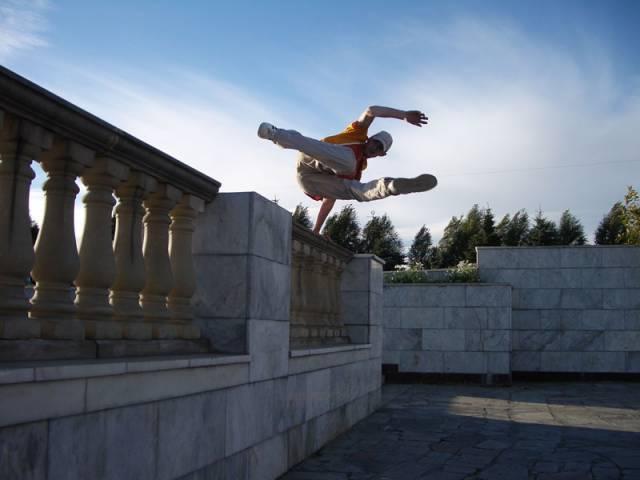 парень прыгает через парапет паркур