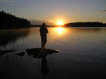 мужчина рыбачит на огромном озере на закате