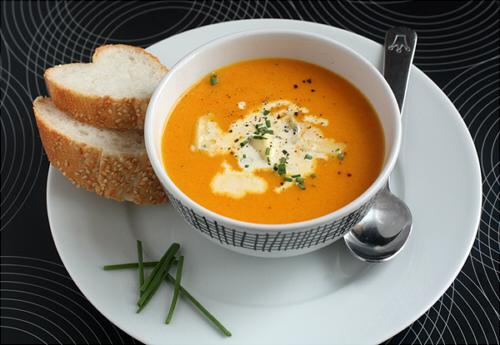 тыквенный суп в пиале на столе на тарелке с куском хлеба ресторан