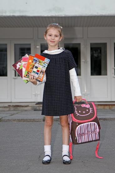 девочка около дверей школы на ступеньках в руках яркие тетради и портфель