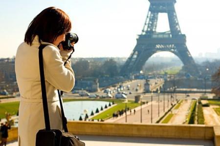 девушка фотограф фотографирует Эйфелеву башню в Париже