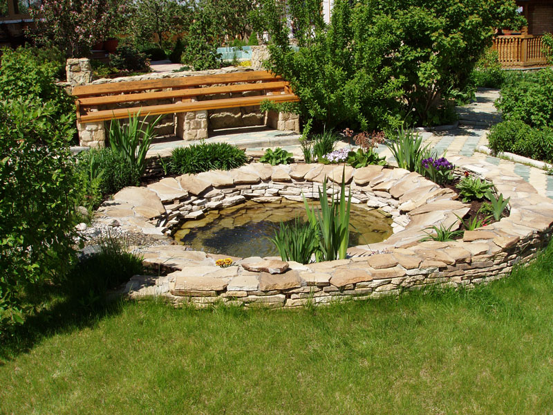 изящно украшенный камнем пруд на участке скамейка зелень
