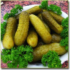 соленые огурцы на тарелке с зеленью