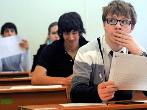 парень в очках в классе за партой волнуется на экзамене