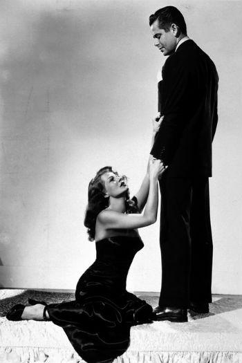 сцена драма в стиле старого Голливуда: красавица-женщина у ног мужчины-франта в костюме