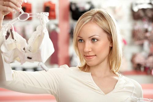 симпатичная девушка-блондинка выбирает белье лифчик бюстгалтер в магазине
