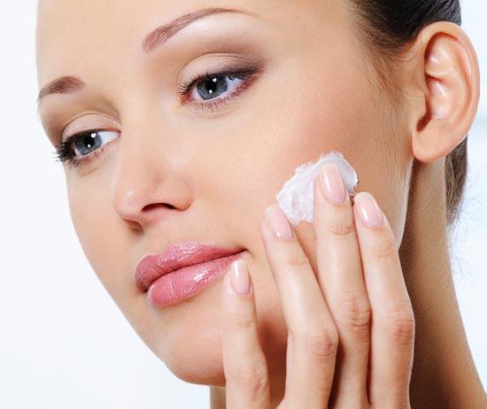 красивая девушка наносит крем на лицо