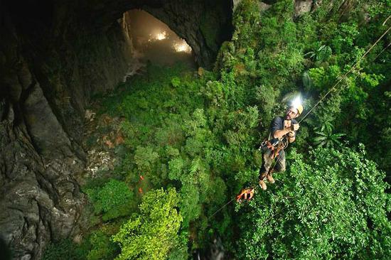 спуск на тросе в самой большой пещере в мире Хан Сон Дунг во Вьетнаме заросли джунгли под землей