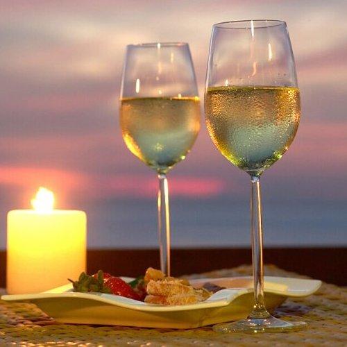 два запотевших бокала на столе свечи ужин закате ночью