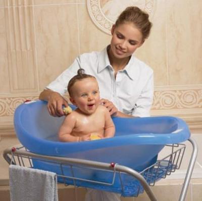 опустить ребенка на несколько сантиметров в чуть теплую воду в детской ванночке