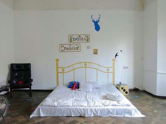 матрас на полу с нарисованной спинкой кровати сзади на стенке