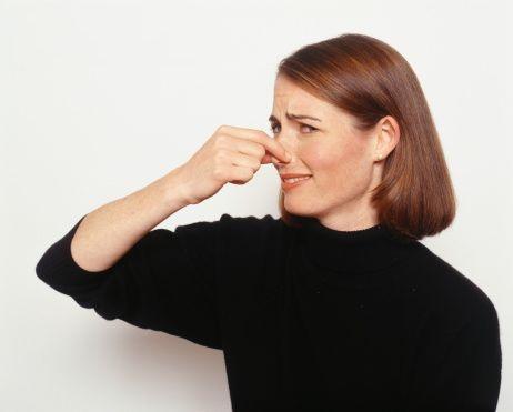 женщина зажимает нос рукой - противный запах