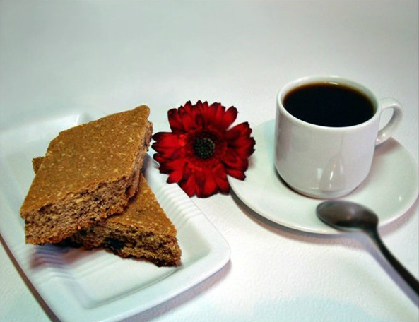 Печенье кофейное или кантуччи в тарелке на столе с цветком герберой и чашкой кофе