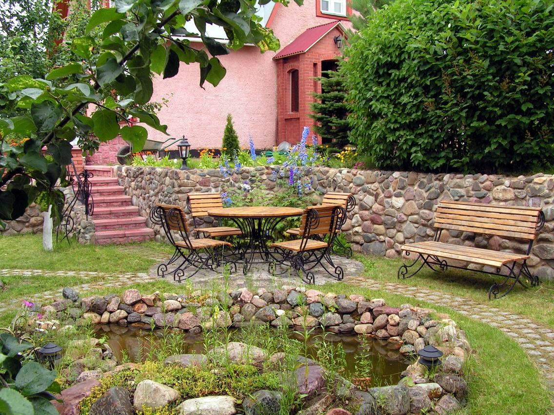 участок около дома дачи кованые из дерева стол и стулья, прудик, выложенный камнем