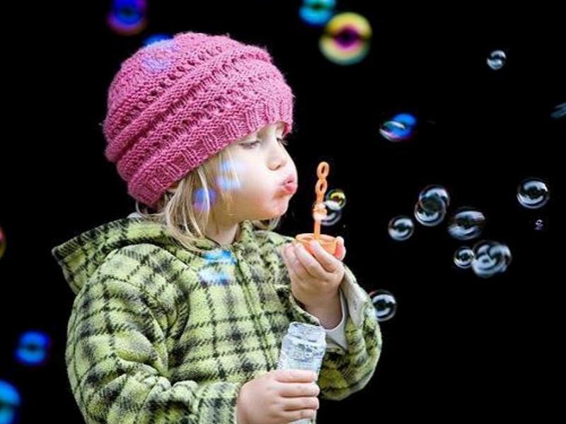симпатичный ребенок девочка пускает мыльные пузыри