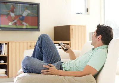 мужчина парень с пультом на кресле напротив телевизора