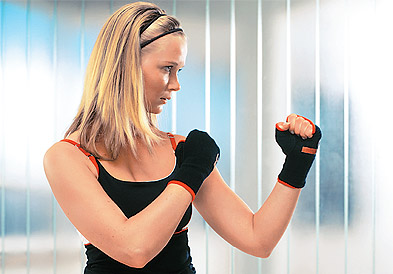 красивая девушка блондинка в спортивном костюме приемы самообороны в защитной стойке