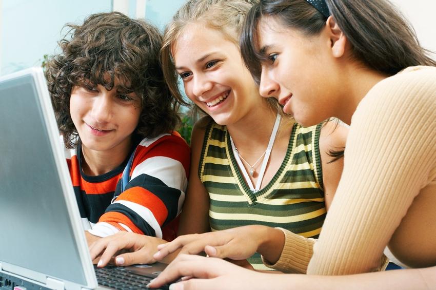 молодежь девушки парень за компьютером увлеченно смотрят