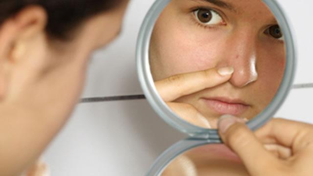 девушка смотрит в саленькое зеркало прыщи на носу
