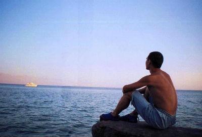 закат парень силит на камне у моря смотрит вдаль