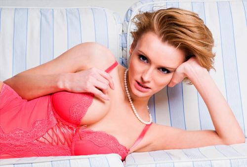 симпатичная девушка блондинка с красивой грудью в розовом белье лежит на диване
