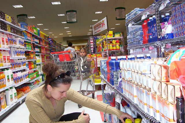 товары на полках в супермаркете женщина выбирает воду, ребенок ждет у тележки с продуктами