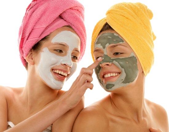 две веселые девушки в косметических масках и полотенцах на головах