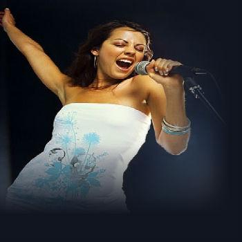 девушка в платье в энтузиазмом поет, взяв микрофон в руку