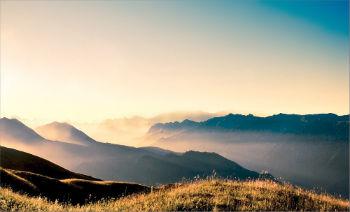 вид на горы и поле с туманом на восходе закате