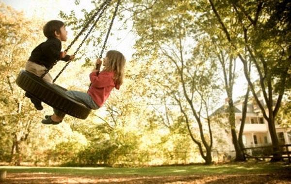 дети качаются на кочелях шине на цепях, закрепленных на дереве на дачном участке