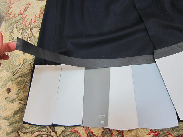 Листы серого оттенка (нарежьте из крупных листов карточки среднего размера, если это требуется) начинаем клеить прозрачным широким скотчем на юбку – сначала по низу внахлест
