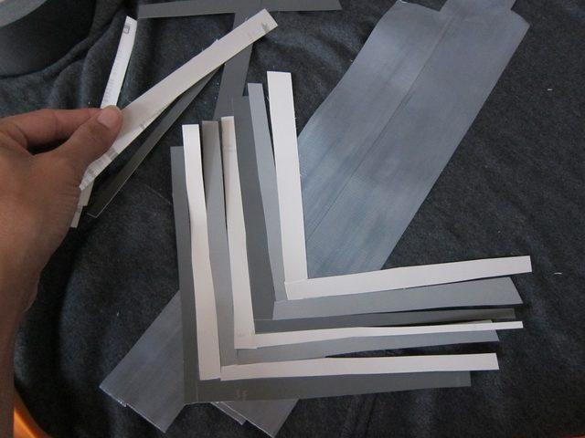 Снова нарезаем полосок разных оттенков серого, но на липкую ленту/ткань накладываем их теперь не поперек, а елочкой/галочкой/уголком вниз – буквой «V»
