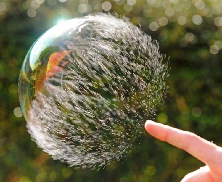 лопает мыльный пузырь пальцем съемки в движении
