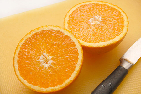 Разрежьте апельсины на половинки