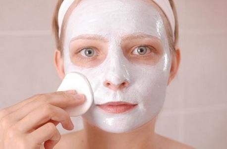 девушка в маске наносит косметическую маску на лицо