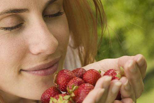 ягоды клубники в горсти: женщина-блондинка вдыхает их запах