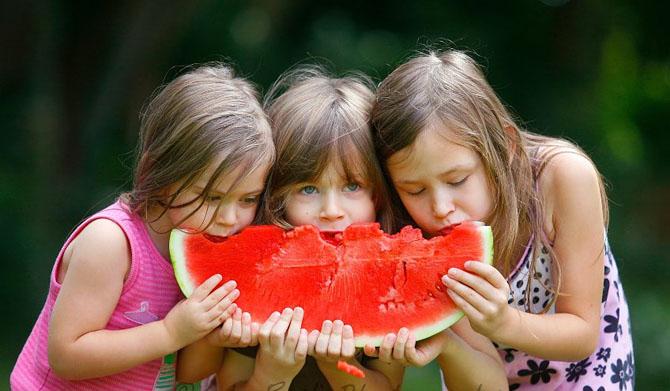 дети едят большую арбузную дольку
