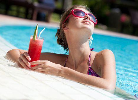 Девушка в бассейне пьет арбузный сок