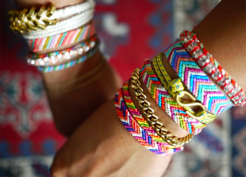 у девушки на руках большое огромное количество браслетов дружбы фенек фенечек