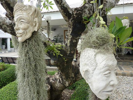 таиландский «райский» Белый Храм (Wat Rong Khun) - головы со мхом в саду