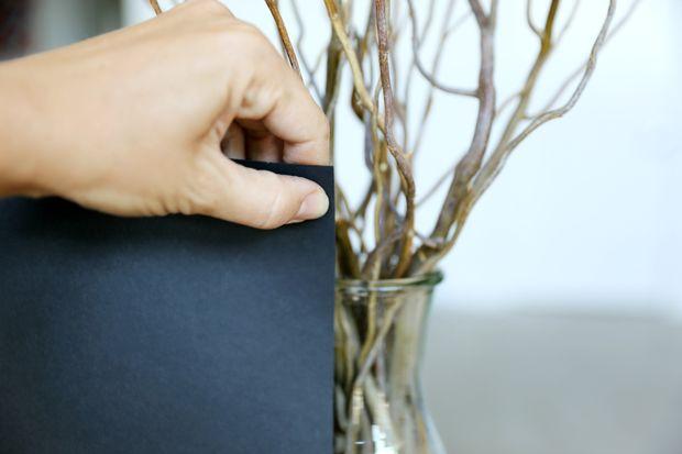 Ставим вертикально лист черной бумаги около контейнера. Отмечаем на бумаге уровень на расстоянии 2,5-5 см над краем горла тары.