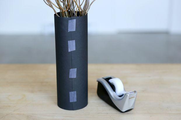 Оборачиваем данный лист туго вокруг вазы, края бумаги сзади вазы накладываем внахлест и в таком положении склеиваем бумагу липкой лентой