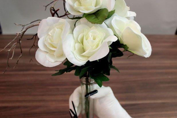 Красиво поставьте в вазу искусственные белые розы, а также подобранную на улице корявую веточку
