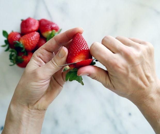 Прежде чем вытащить нож из разреза, немного отогните полученный «лепесток» вбок, чтобы этот кусочек клубники чуть выпирал