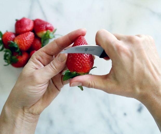 Используя нож для чистки овощей, прорежьте край бока ягоды ровно вниз почти до самого ее основания с зеленью